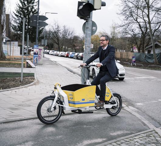 Herr Knopp, Ansprechpartner für Mobilitätskonzepte bei der GWG München, auf einem GWG-Lastenrad.