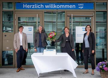 4 Personen stehen vor den Türen der GWG-Hausverwaltung und lächeln in die Kamera.